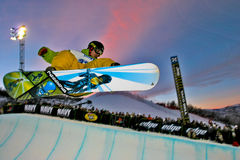 Snowboarder jumping. Pro snowboarder jumping from a half pipe during night session in Aspen, Colorado Stock Image