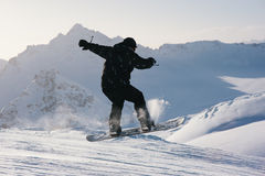 Snowboarder jumping from  slope on  background of mountains Royalty Free Stock Photo