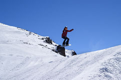 Snowboarder jumping in snow park at ski resort on sun winter day Royalty Free Stock Image