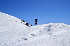 Snowboarder jumping in snow park at ski resort on sun winter day. Caucasus Mountains, region Dombay Stock Image