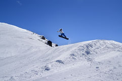 Snowboarder jumping in snow park at ski resort on sunny winter d. Ay. Caucasus Mountains, region Dombay Royalty Free Stock Images