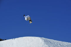 Snowboarder jumping from a snow ramp Stock Image