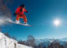 Snowboarder is jumping with snowboard from snowhill. Snowboarder in red suit is jumping with snowboard from snowhill stock photography