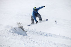 Snowboarder jumping on a snowy slope. Young male snowboarder jumping on a snowy slope Stock Images