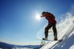 Snowboarder jumping from the springboard against the sky Stock Image