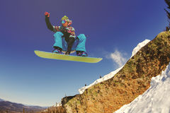 Snowboarder jumping from the springboard against the sky Stock Images