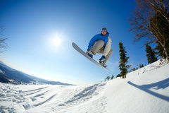 Snowboarder jumping from the springboard against the sky Stock Photography