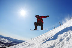 Snowboarder jumping from the springboard against the sky Royalty Free Stock Images