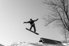 Snowboarder jumping from a springboard. Male snowboarder jumping from a springboard. Snowboarder performs tricks on a snowboard on a sunny winter day Royalty Free Stock Image