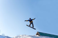 Snowboarder jumping from a springboard. Male snowboarder jumping from a springboard. Snowboarder performs tricks on a snowboard on a sunny winter day Stock Photo