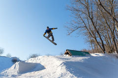 Snowboarder jumping from a springboard. Male snowboarder jumping from a springboard. Snowboarder performs tricks on a snowboard on a sunny winter day Stock Photos