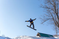 Snowboarder jumping from a springboard. Male snowboarder jumping from a springboard. Snowboarder performs tricks on a snowboard on a sunny winter day Royalty Free Stock Photo
