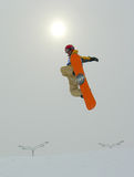Snowboarder Jumping and sun. Behind head royalty free stock images