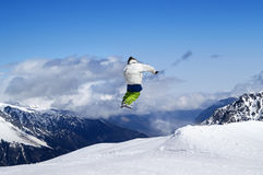 Snowboarder jumping in terrain park at ski resort on sun winter. Day. Caucasus Mountains, region Dombay Stock Photos
