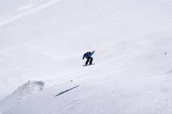 Snowboarder jumping in terrain park at ski resort on sun winter. Day. Caucasus Mountains, region Dombay Stock Photography