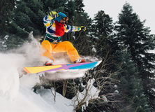 Snowboarder is jumping very high and freeriding from hill in the mountain forest. Snowboarder with special equipment is jumping very high and freeriding from Stock Photos