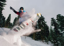 Snowboarder is jumping very high and freeriding from hill in the mountain forest. Snowboarder with special equipment is jumping very high and freeriding from Royalty Free Stock Photo