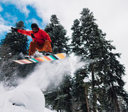 Snowboarder is jumping very hight and freeriding from the hill in the mountain forest. Snowboarder with special equipment is jumping very high and freeriding Stock Photography