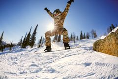 The snowboarder jumps from the springboard against the blue sky Stock Images