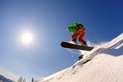 The snowboarder jumps from the springboard against the blue sky Stock Photography