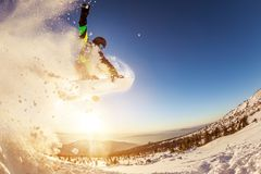 Snowboarder jumps against sunset sun royalty free stock images