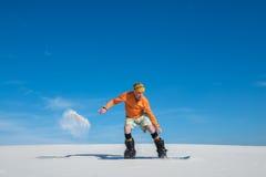 Snowboarder ląduje po skoku na piaska skłonie Zdjęcie Stock