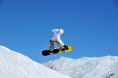 Snowboarder landing after a jump. A snowboarder having performed a jump comes into land on a ramp. In the background snow covered mountains Stock Images