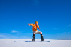 Snowboarder lands after jumping on a sand dune Stock Image