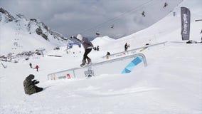 Snowboarder maakt dia op ijzer op helling slepen Landschap cameraman SNEEUW BERGEN competition stock videobeelden