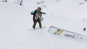 Snowboarder maakt dia op ijzer op helling slepen Landschap SNEEUW BERGEN Extreme sport wedstrijd stock video