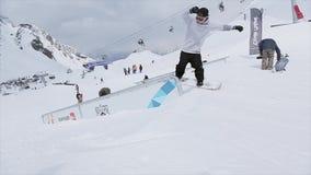 Snowboarder maakt dia op ijzer op helling slepen Mensen SNEEUW BERGEN competition wedstrijd stock videobeelden