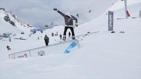 Snowboarder maakt terug dia op ijzer op helling slepen Landschap SNEEUW BERGEN competition wedstrijd stock footage