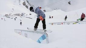 Snowboarder maakt terug dia op ijzer op helling slepen Mensen SNEEUW BERGEN competition uitdaging stock footage