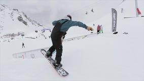 Snowboarder maakt terug dia op ijzer op helling slepen Mensen SNEEUW BERGEN competition wedstrijd stock footage