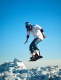 Snowboarder making jump against the blue sky Stock Photo