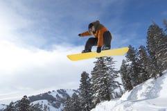 Snowboarder maschio che salta sopra la collina innevata Immagine Stock
