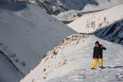 Snowboarder maschio di Freeride che sta sul picco di montagna immagine stock