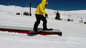 Snowboarder masculino profissional que desliza a inclinação em declive da neve que salta na paisagem do inverno do conluio do per video estoque
