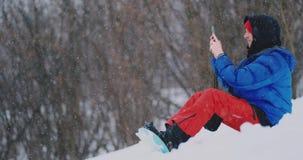 Snowboarder masculino que senta-se na neve que toma fotos no cenário bonito do telefone do recurso para redes sociais filme