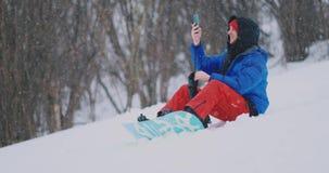 Snowboarder masculino que senta-se na neve que toma fotos no cenário bonito do telefone do recurso para redes sociais vídeos de arquivo