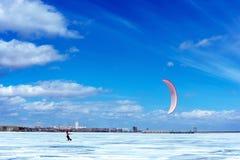 Snowboarder med en drake på havet i vintern arkivbild