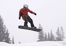 Snowboarder In Mid-Air. A snowboarder with a red coat getting big air in a jump. It was snowing heavily and the snowflakes are motion-blurred as I panned with stock image