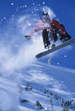 Snowboarder In Midair With Snow Powder Trailing Behind. Low angle view of a snowboarder in midair with snow powder trailing behind above ski slope stock images