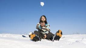 Snowboarder mit einem langen Haar, das auf einem Snowboard und einen Schneeball in der Luft werfen sitzt Extremer Wintersport stockfotos