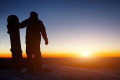 Snowboarder on the mountain during sunset. Holding a snowboard Stock Image