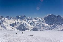 Snowboarder in the mountains. Snowboarder on the slope in front of a majestic mountain chine view Royalty Free Stock Images