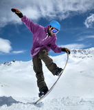 Snowboarder in mountains. Taking for the edge snowboard against the blue sky and clouds stock images