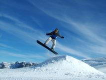 Snowboarder in the mountains. Picture of a snowboarder jumping from slope stock image