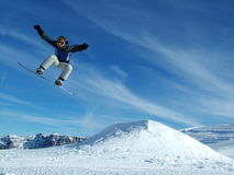 Snowboarder in the mountains. Picture of a snowboarder jumping from slope royalty free stock images