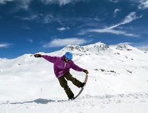 Snowboarder in mountains. Taking for the edge snowboard against the blue sky and clouds Stock Photography
